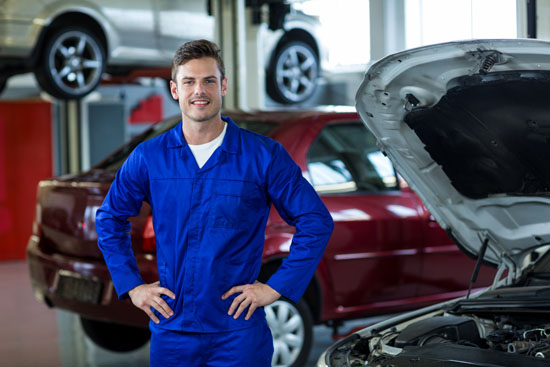 Portrait of smiling mechanic standing with hands on hip in repair shop